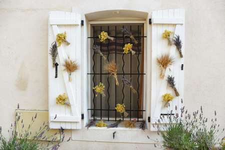 Medieval window with ornaments and lavender flowers in Valensole village, Provence, France