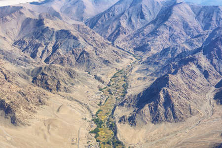Aerial view of desert landscape in Ladakh region from the airplane window, India.