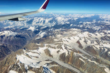 Aerial view of glaciers and himalayas in Ladakh region from the airplane window, India.