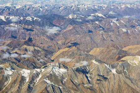 Aerial view of desert and himalayas in Ladakh region from the airplane window, India.
