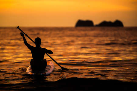 A relaxing, peaceful, paddle boarder in Costa Rica enjoying a golden sunset. Imagens