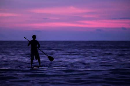 コスタリカの夕日に海でパドル ボードを漕ぐ男 写真素材