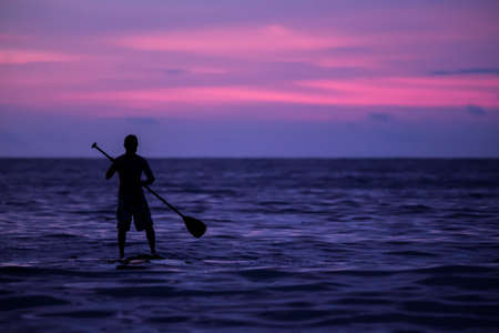 a man rowing a paddle board on the ocean into the Costa Rican sunset