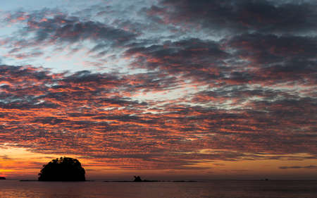 blanketed: A small dark island of trees in the ocean blanketed by clouds lit by a beautiful orange and red sunset