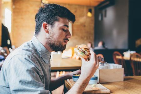 volto uomo: Studen sta mangiando in un locale e godendo fast food