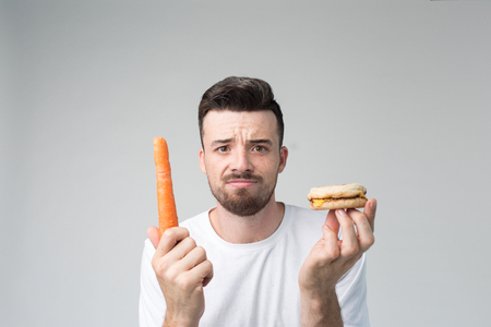 Man makes the choice between fast and healthy food. Tasty or useful The dilemma choosing a different lifestyle
