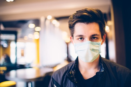 Man wearing medical face mask in the a restaurant. Male wearing face mask, protection from virus infection.