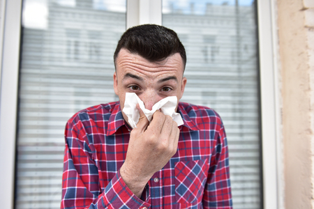 picture from a young man with handkerchief. Sick guy has runny nose. man makes a cure for the common cold Stock Photo