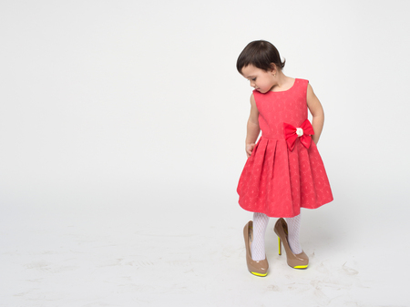 Funny toddler girl with black hair wearing a rad dress is trying on her mothers high heels shoes isolated on white background Stock Photo