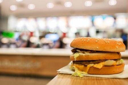 cheeseburger on the table. On the background of of fast food restaurants.