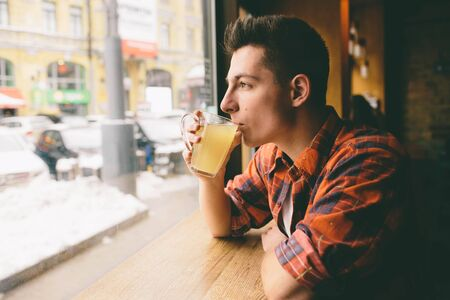 Young student is sitting in the restaurant and taste a warm drink. man drinking  tea at the cafe Stock Photo