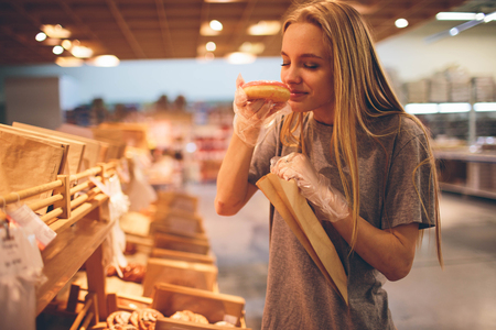Young woman chooses bread in the store