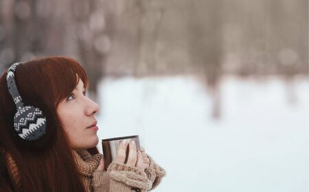 Winter. Woman with red hair wearing ear muffs. Girl drinking hot tea or coffee iron insulated cup