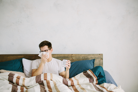 cold cure: young man with handkerchief. Sick guy on the bed has runny nose. man makes a cure for the common cold Stock Photo