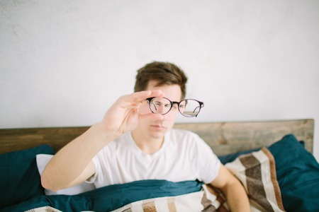 Closeup portrait of young man with glasses. He has eyesight problems and is squinting his eyes a little bit. Handsome guy is holding his eyeglasses right in front of camera with one hand Stockfoto