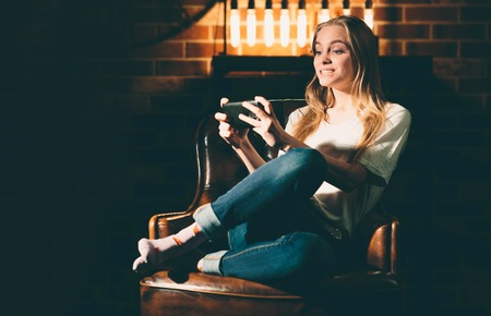 Girl in a cozy dark room holding a phone and searches the interenet. Blonde and warm lamp light Stock Photo