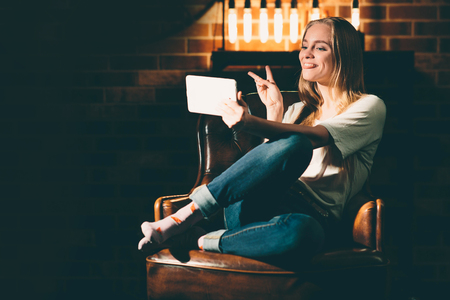 Girl in a cozy dark room holding the tablet and searches the interenet. Blonde and warm lamp light