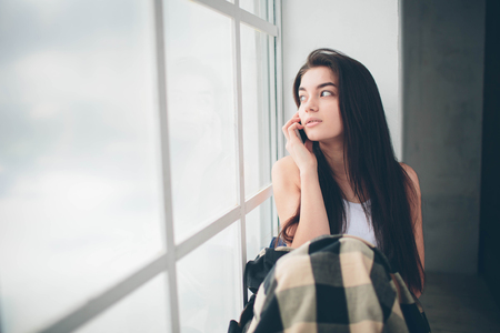 A young woman with black hair in a white T-shirt at a window flooded with sunlight uses a smartphone, communicates and searches for information on the Internet or social networks