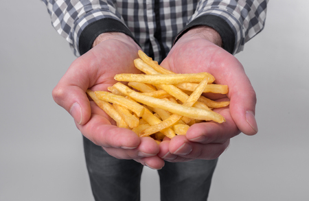 man holds in his hands a tasty fries Stock Photo