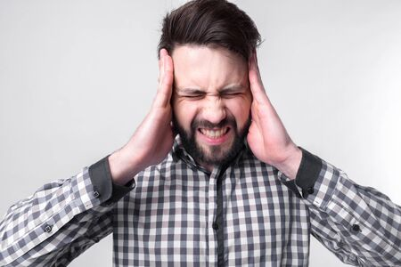 studenh holding his head with his hands. Businessman gets stress. Bearded man on a white background