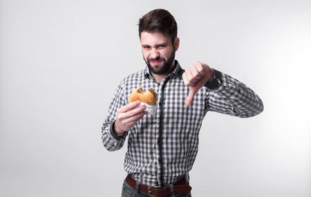 Al hombre no le gusta la hamburguesa. estudiante come comida rápida. comida no útil. muy hambriento Foto de archivo - 77618807