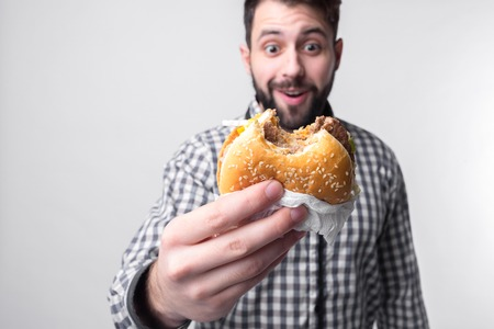 man holding a piece of hamburger. student eats fast food. not helpful food. very hungry guy