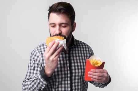 man holding a piece of amburger and french fries . student eats fast food. not helpful food. very hungry guy Stock Photo