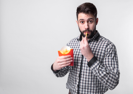 man holding a french fries . student eats fast food. not helpful food. very hungry guy