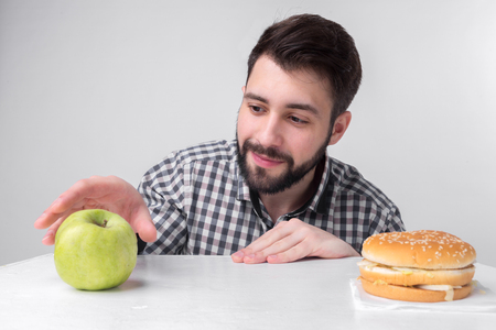 Bearded man in checkered shirt on a light background holding a hamburger and an apple. Guy makes the choice between fast and healthy food. Tasty or useful The dilemma Stock Photo