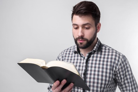 A man in a checkered shirt holding a black book on a light background. Bearded student.