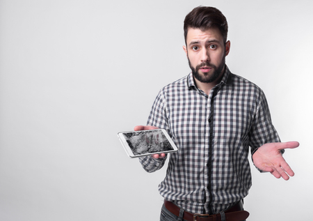 Bearded upset man holds a out-of-use tablet or smartphone. Isolated on a light background