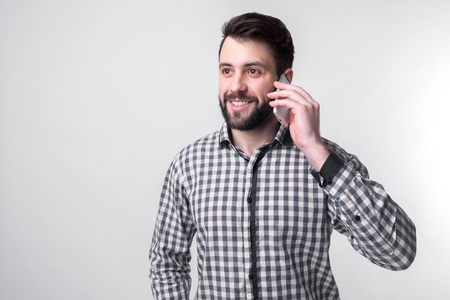 Bearded man in shirt speaks by phone on white background