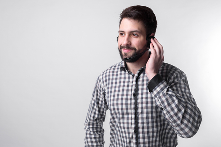 Assistance by telephone. The employee call center helps its customers over the phone. Bearded man isolated on white background.