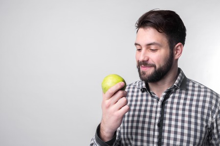 Men eats an apple. bearded guy holding an apple. vegetarian preparing dinner