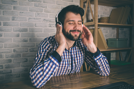 The man is wearing headphones, he sits at home at the computer and listens to music Stock Photo