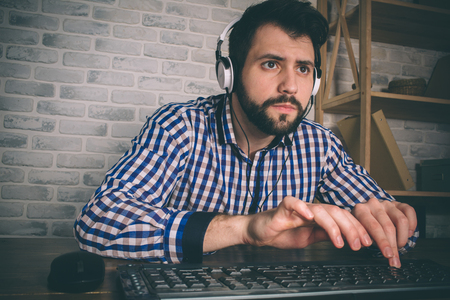 Bearded man playing at home and streaming. Funny guy is excited because of seen virtual video. He is wearing red headphones Stock Photo