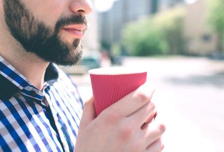 A bearded man enjoys a morning coffee on the street