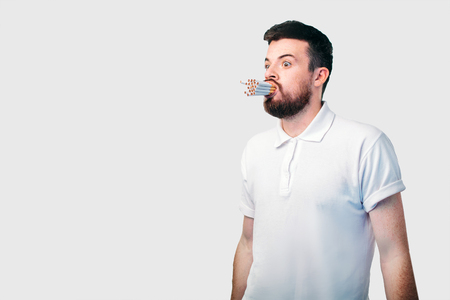 smoking concept. The bearded dark-haired guy holds a lot of cigarettes in his mouth. Stock Photo