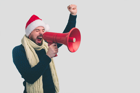 portrait of man in a Christmas hat shouting using megaphone over background Nerd is wearing glasses