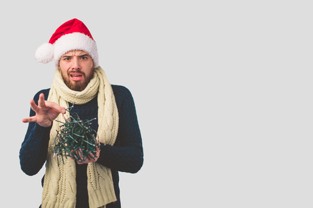 Man in a Christmas hat holds electric garlands. He is very confused Banco de Imagens
