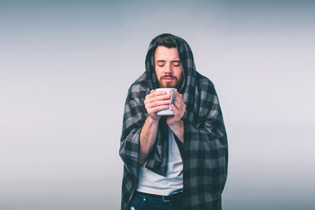 wrapped in the warm blanket or plaid, sick, young snotty man in glasses drinking warm healing tea Stock Photo