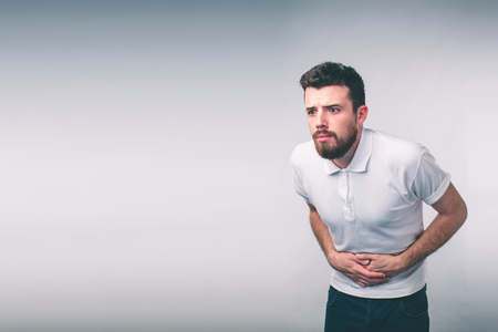 young man having a stomachache..Close up of male body isolated on White Background.