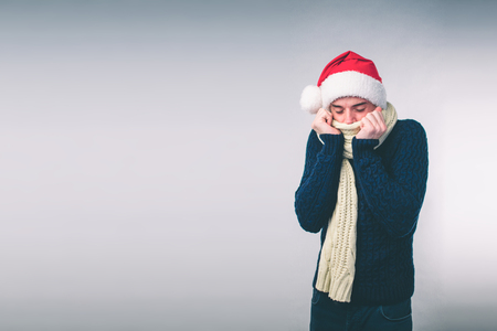 Young man in sweater feel cold over a white background