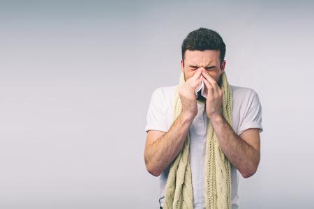 손수건 가진 젊은 남자에서 스튜디오 그림입니다. 고립 된 아픈 사람은 콧물이있다. 남자는 감기약을 치료합니다. 멋쟁이는 안경을 쓰고 있습니다.