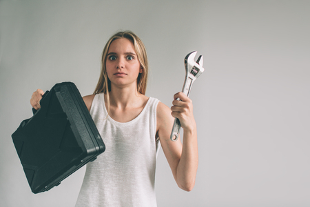 Funny portrait upset craftswoman. Blonde woman is wearing shirt isolated on white. Girl does not know how to use a drill