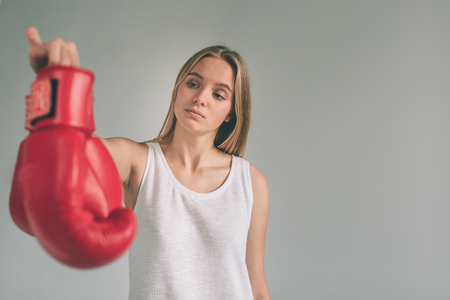 Cowardly funny young woman in red boxing gloves.