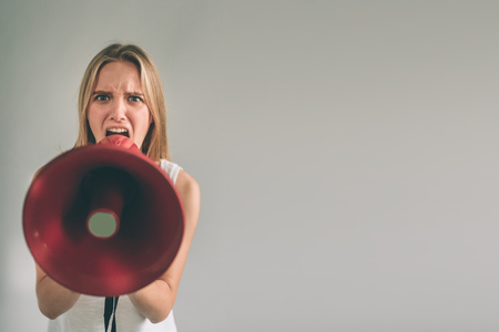 Portrait of young women shouting using megaphone over background Girl in white shirt, studio shot . Stockfoto