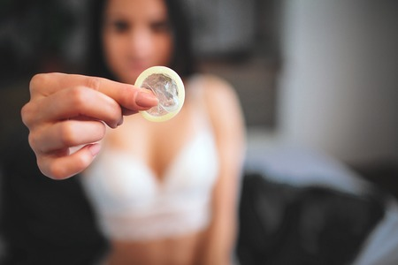 Woman showing a condom on bed, Focus on the condom in the foreground
