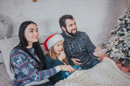 Merry Christmas and Happy New Year . Young family celebrating holiday at home. The Father is holding the remote from the TV. Dad, daughter and mother are watching television. Stock Photo
