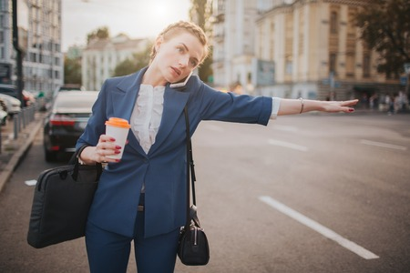 oung stylish businesswoman with coffee cup catching a taxi. Woman doing multiple tasks. Multitasking business woman.